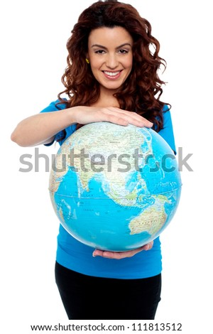 Cheerful girl holding globe safely with both hands. Holding from top and bottom. - stock photo