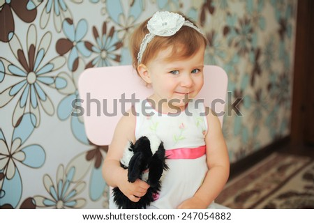 cheerful girl holding rabbit toy - stock photo