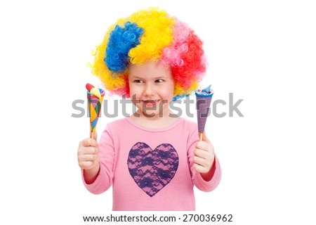 cheerful girl in clown wig playing with bright toys - stock photo