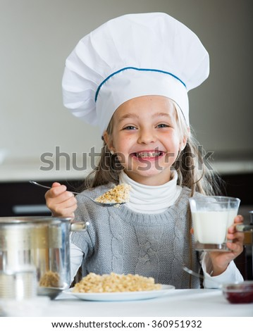 Cheerful girl in cook cap eating porridge and drink milk   - stock photo