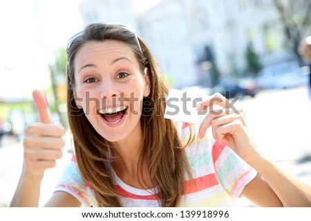 Cheerful girl in showing tourist pass - stock photo
