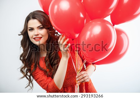 Cheerful girl is holding colored balloons in her arms. She is peeping though it with interest and smiling. Isolated on grey background - stock photo