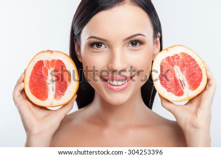 Cheerful girl is holding two parts of grapefruit near her face. She is smiling and looking forward with happiness. Isolated on background - stock photo
