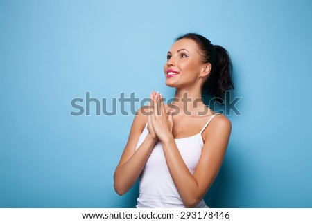 Cheerful girl is joining her palms together with hope. She is asking for help and smiling. Isolated on blue background and there is copy space in left side - stock photo