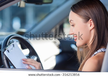 Cheerful girl is sitting at steering wheel of her car. She is holding a folder of documents and reading it with concentration. The lady is smiling