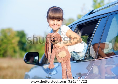 Cheerful girl is standing in car and smiling. She is pushing her body through window outside. The girl is holding toy and looking forward playfully - stock photo