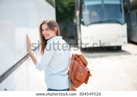 Cheerful girl is standing near a bus and leaning her hand on it. She is looking at the camera with happiness and smiling. The lady is waiting for the bus departure. Copy space in right side - stock photo