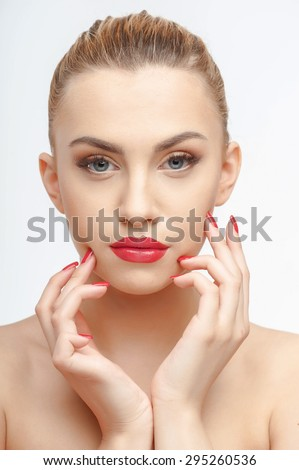 Cheerful girl is touching her face with both her hands gently. She is looking at the camera confidently. Isolated on background - stock photo