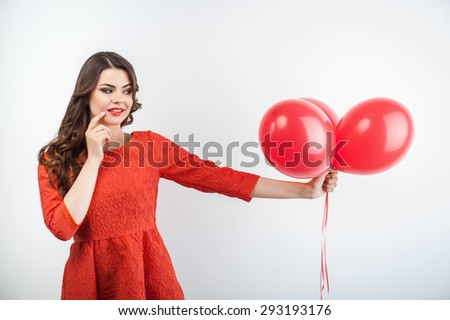 Cheerful girl is viewing red balloons. She is holding it in her arm. She is disappointed. Isolated on grey background - stock photo