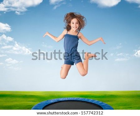 cheerful girl jumping on a meadow  on trampoline - stock photo