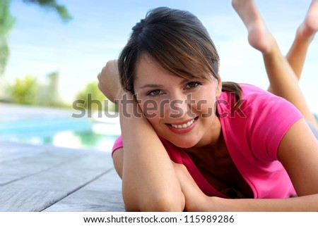 Cheerful girl laying on pool deck after exercising - stock photo