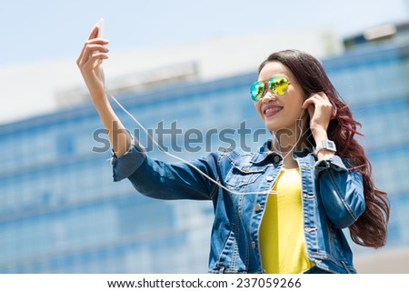 Cheerful girl listening to the music and talking selfie - stock photo