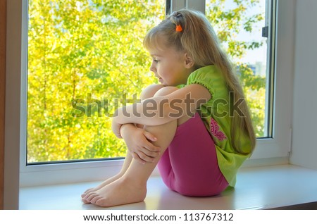 Cheerful girl looking at the beautiful trees outside the window. - stock photo