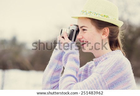 cheerful girl photographer takes on an old camera in winter - stock photo
