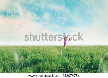 Cheerful girl playing among soap bubbles on green meadow in summer - stock photo