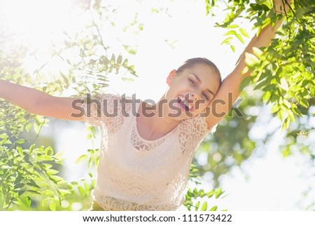 Cheerful girl playing in foliage in forest - stock photo