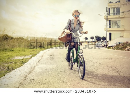Cheerful girl riding a bike  - stock photo
