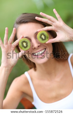 Cheerful girl showing kiwi slices - stock photo