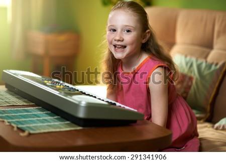 cheerful girl sits near an electronic piano - stock photo