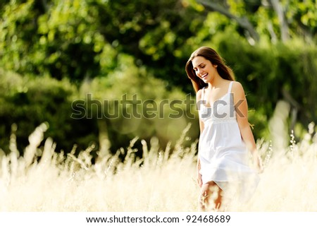 cheerful girl walks outside in a meadow and is happy - stock photo