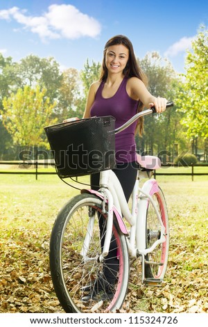 Cheerful girl with a bicycle enjoying nature in the park. - stock photo