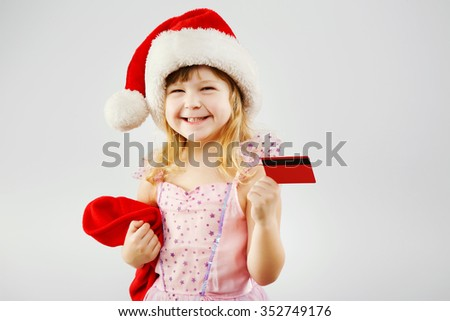 Cheerful girl, with curly blond hair, wearing on pink dress and red santa hat, holding red bag for presents and credit card in her hands, on white background, in studio, waist up - stock photo