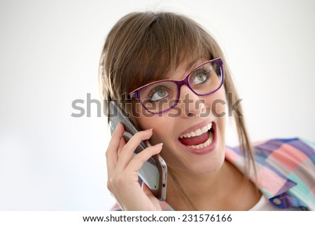 Cheerful girl with eyeglasses talking on phone - stock photo