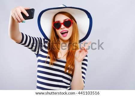 Cheerful girl with hat and striped T-shirt wearing heart-shaped red sunglasses, holding phone and smiling. Summer look. Studio, indoor, head and shoulders - stock photo