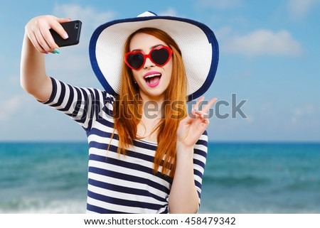 Cheerful girl with hat and striped T-shirt wearing heart-shaped red sunglasses, holding phone and smiling. Summer look. Against the background of the sea, head and shoulders - stock photo