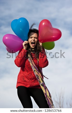 cheerful girl with heart shape balloons against blue sky background - stock photo