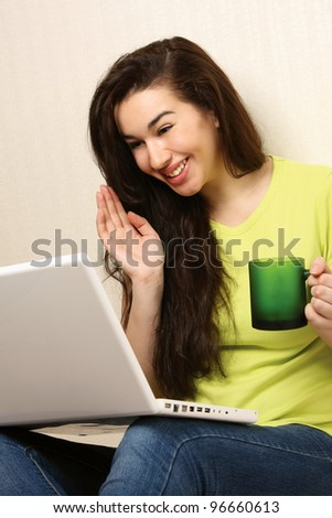 Cheerful girl with laptop sitting on floor near wall