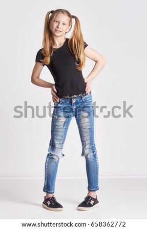 Cheerful girl with long pigtails posing on light background. Bright positive emotions, a smile on her face. Teen girl
