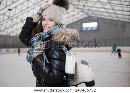Cheerful girl with skates on ice skating rink  - stock photo