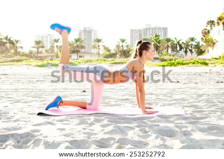 cheerful girl working out on the beach. fitness instructor making exercise. - stock photo