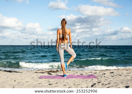 cheerful girl working out on the beach. fitness instructor making exercise.