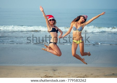 cheerful girlfriends in a santa hat and bikini jumping on the beach