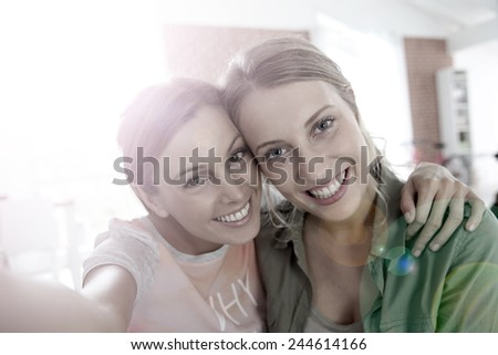 Cheerful girlfriends taking picture of themselves - stock photo