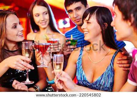 Cheerful girls and guys with martini and champagne having fun at party