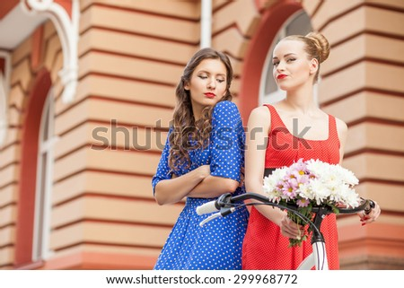 Cheerful girls are cycling in town. The blond girl is riding bicycle and holding flowers greedily. Her friend crossed hands with resentment and looking at bucket jealously. Copy space in left side - stock photo