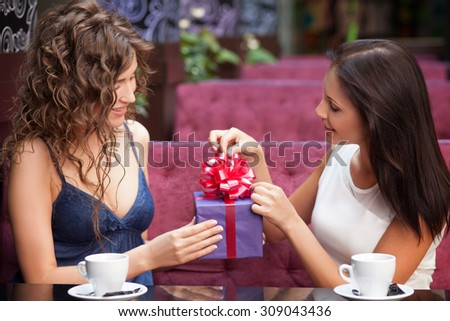 Cheerful girls are sitting at the table in cafeteria. They are drinking coffee and smiling. One lady is giving a present to her friend. Another woman is opening the box with interest - stock photo