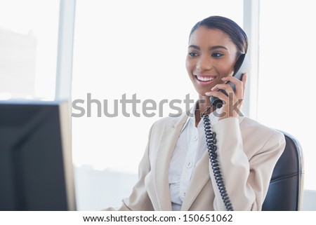 Cheerful gorgeous businesswoman on the phone in bright office - stock photo