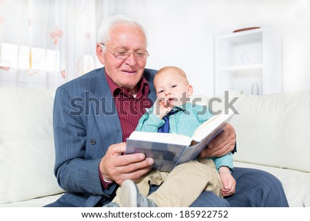 Cheerful grandfather and grandson sitting on the sofa, and reading book