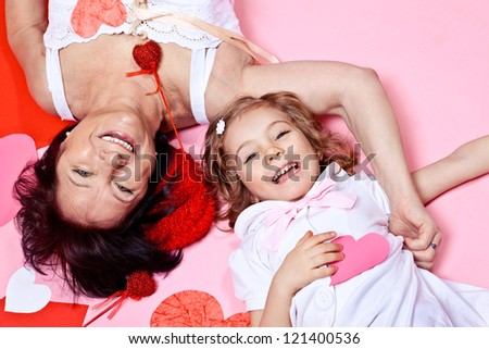 Cheerful grandmother and granddaughter lying with paper hearts - stock photo
