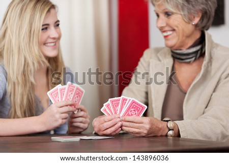 Cheerful grandmother and granddaughter playing cards at home - stock photo
