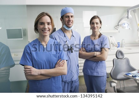 Cheerful group of dentists and their assistants standing in the dental office and looking at camera. - stock photo