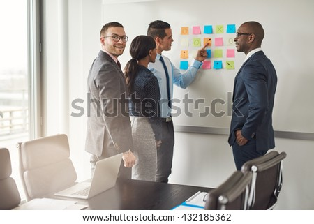 Cheerful group of diverse business people in conference meeting using colorful sticky notes to organize ideas on large white board - stock photo