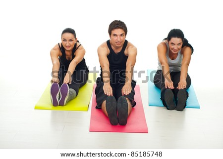 Cheerful group of fitness people stretching their bodies  and sitting on colorful mats - stock photo