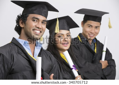 Cheerful Group of Indian college graduates wearing cap and gown holding diploma on white background - stock photo