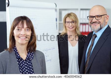Cheerful group of three mature business executives standing together around large paper grid chart in office with shelf in background - stock photo