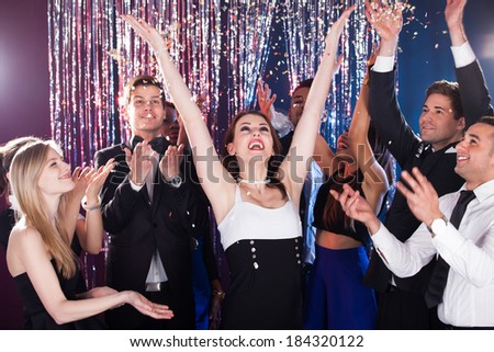 Cheerful group of young friends celebrating in nightclub - stock photo